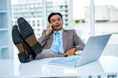 Homme d'affaires au téléphone avec ses pieds sur son bureau Photo stock