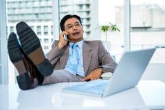 Homme d'affaires au téléphone avec ses pieds sur son bureau Photos libres de droits