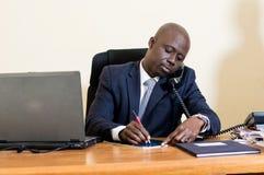 Homme d'affaires au téléphone au bureau Image stock