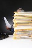 Homme d'affaires au téléphone derrière la pile de fichiers Photographie stock