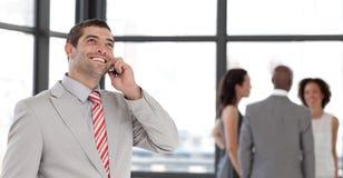 Homme d'affaires au téléphone devant l'équipe d'affaires Photos stock