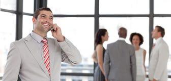 Homme d'affaires au téléphone devant l'équipe d'affaires Photo libre de droits