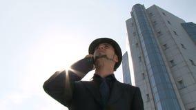 Homme d'affaires au téléphone devant l'immeuble de bureaux clips vidéos