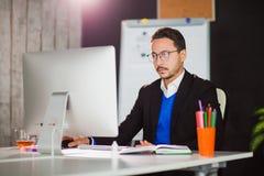 Homme d'affaires au travail de bureau avec le moniteur d'ordinateur Image stock