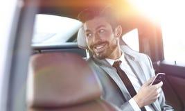 Homme d'affaires austère s'asseyant dans le siège arrière dans sa voiture photo stock