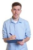 Homme d'affaires australien heureux avec la note d'écriture de presse-papiers Photos stock