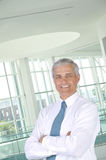 Homme d'affaires avec des bras pliés dans la configuration de bureau Photos libres de droits