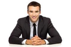 Homme d'affaires avec des bras se penchant sur la table Photographie stock libre de droits