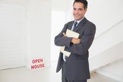 Homme d'affaires avec des documents à une maison à vendre Image stock