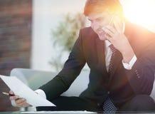 Homme d'affaires avec des documents sur un fond trouble de bureau Photographie stock