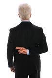 Homme d'affaires avec des doigts croisés Photo stock
