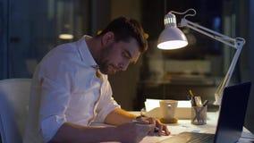 Homme d'affaires avec des dossiers et fonctionnement d'ordinateur portable la nuit clips vidéos