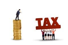 Homme d'affaires avec des employés soulevant un texte d'impôts Photographie stock libre de droits