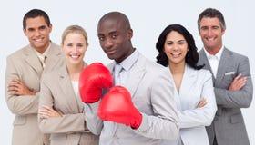 Homme d'affaires avec des gants de boxe aboutissant son équipe Photo stock
