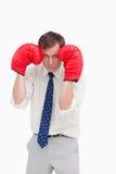 Homme d'affaires avec des gants de boxe prenant le cache image stock