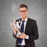 Homme d'affaires avec des glaces retenant un grand trophée Image stock