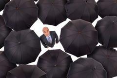Homme d'affaires avec des parapluies Image stock
