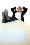 Homme d'affaires avec des pieds sur le Tableau Image libre de droits