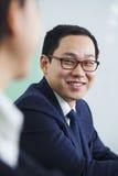 Homme d'affaires avec des verres souriant au collègue Photographie stock