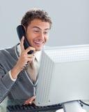Homme d'affaires avec du charme au téléphone à son bureau Image stock
