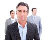 Homme d'affaires avec du charme posant devant son équipe Photographie stock libre de droits
