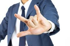 Homme d'affaires avec je t'aime le geste de main de signe d'isolement sur le blanc Image stock