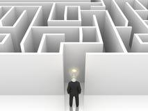Homme d'affaires avec l'ampoule devant un labyrinthe mystérieux Image stock