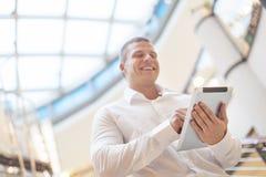 Homme d'affaires de sourire avec l'ordinateur de comprimé dans le buil moderne d'affaires Photographie stock libre de droits