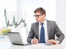 Homme d'affaires avec l'ordinateur, les papiers et la calculatrice photographie stock libre de droits