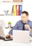 Homme d'affaires avec l'ordinateur portable dans le bureau Photo libre de droits