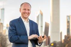 Homme d'affaires avec l'ordinateur portable devant des immeubles de bureaux Photographie stock