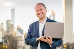Homme d'affaires avec l'ordinateur portable devant des immeubles de bureaux Photo libre de droits