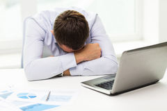 Homme d'affaires avec l'ordinateur portable et les papiers dans le bureau Photo stock