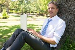Homme d'affaires avec l'ordinateur portable se penchant sur l'arbre Photos stock