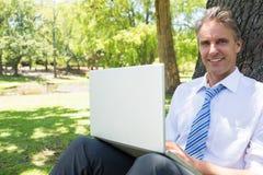 Homme d'affaires avec l'ordinateur portable se penchant sur le tronc d'arbre Photographie stock libre de droits