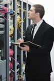 Homme d'affaires avec l'ordinateur portatif dans la pièce de serveur de réseau Photographie stock libre de droits