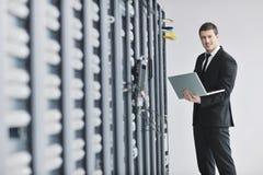 Homme d'affaires avec l'ordinateur portatif dans la pièce de serveur de réseau Image stock