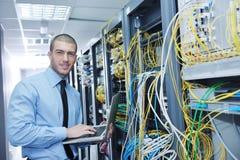 Homme d'affaires avec l'ordinateur portatif dans la pièce de serveur de réseau photographie stock
