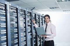 Homme d'affaires avec l'ordinateur portatif dans la pièce de serveur de réseau Image libre de droits