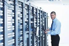 Homme d'affaires avec l'ordinateur portatif dans la pièce de serveur de réseau Photos stock