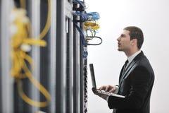 Homme d'affaires avec l'ordinateur portatif dans la pièce de serveur de réseau Images stock