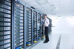 Homme d'affaires avec l'ordinateur portatif dans la pièce de serveur de réseau Images libres de droits