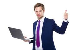 Homme d'affaires avec l'ordinateur portatif et le pouce vers le haut Image stock