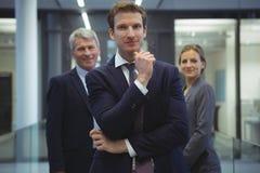 Homme d'affaires avec la main sur le menton se tenant dans le bureau Photo stock