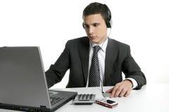 Homme d'affaires avec la musique de mp3 d'audition d'ordinateur portatif Photographie stock