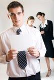 Homme d'affaires avec la note-carte blanc et deux femmes d'affaires Photos stock