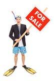 Homme d'affaires avec la prise d'air se tenant pour le signe de vente Image stock