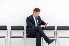 Homme d'affaires avec la séance mobile dans le couloir de bureau photographie stock libre de droits
