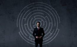Homme d'affaires avec la serviette se tenant au-dessus du fond de labyrinthe B Image stock