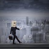 Homme d'affaires avec la tête de carton sur le dessus de toit Image stock